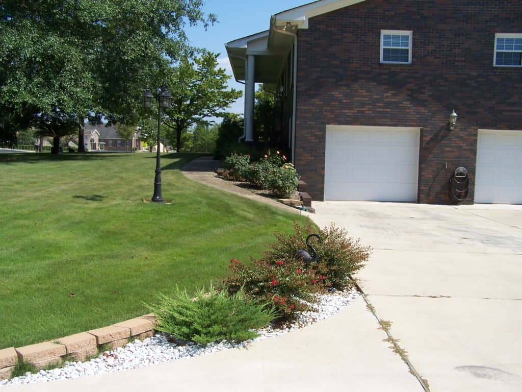End view of a brick house with 2 white garage doors and cement driveway.