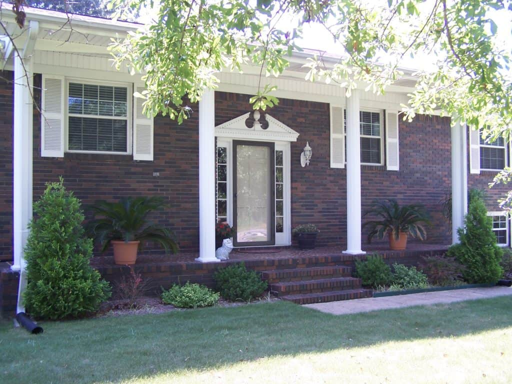 Brick house with long front porch supported by 4 white columns, white front door and white shutters on the windows.