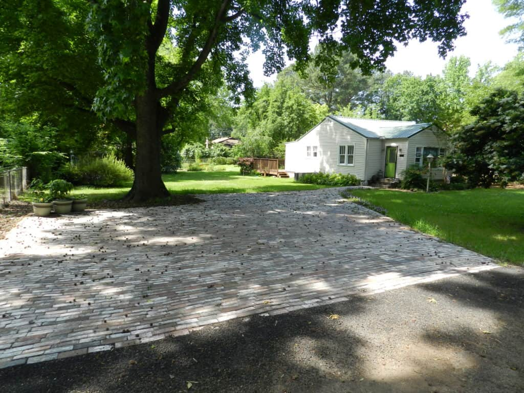 Brick driveway under a huge sweet gum tree and beside vinyl sided house with green metal roof and bright green door.