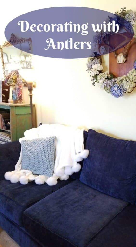 Decorating with Antlers, Hydrangea wreath surround 8 point deer antlers hanging on wall behind navy blue sofa