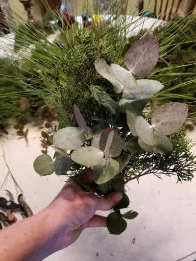 hand holding a bundle of greenery made up of cedar, eucalyptus and pine