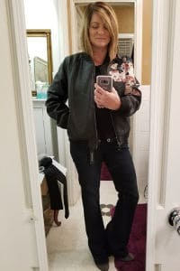 Edgy Stitch fix style for over 50, Black Pleather jacket with embroidered flowers, black top with grommet detail, black jeans