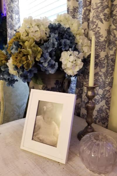 vignette on white table with crock of hydrangeas, white photo frame and silver candlestick