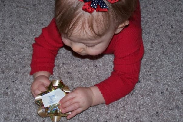 Baby playing with bow off gift