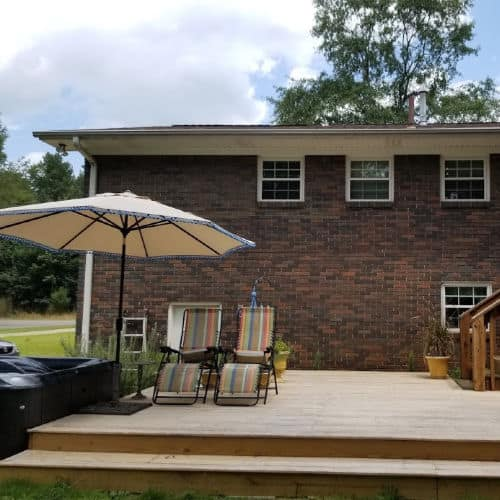 Hot tub, lounge chairs and umbrella on wood deck