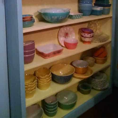 Blue bookshelf with yellow shelves filled with bowls